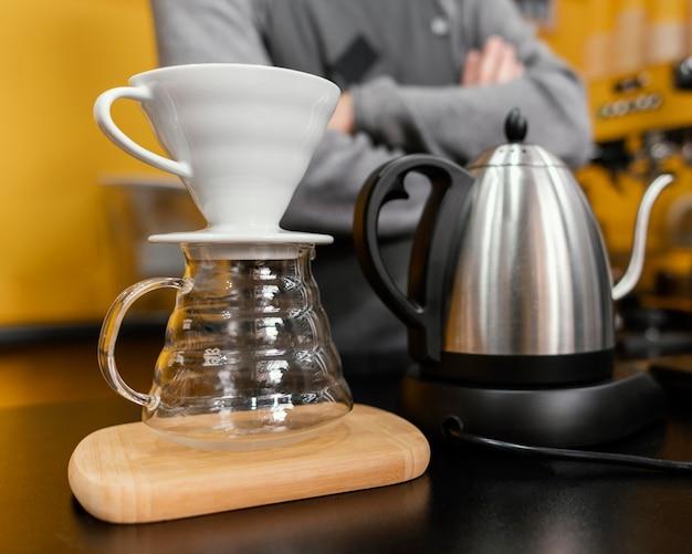 Męski barista przygotowuje kawę z czajnikiem i filtrem