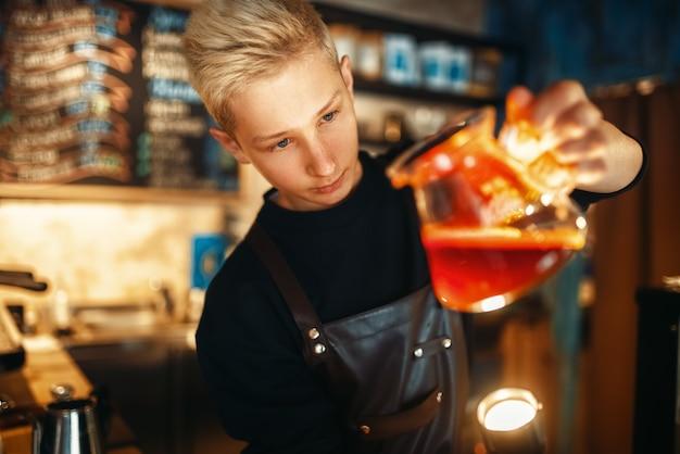 Męski barista sprawdza osad w dzbanku do kawy
