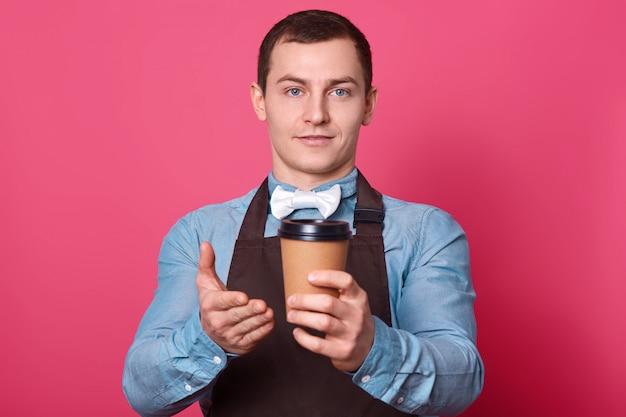 Męski barista sugeruje skosztowanie aromatycznej kawy przez niego przygotowanej, pokazuje z jednorazową filiżanką gorącego napoju