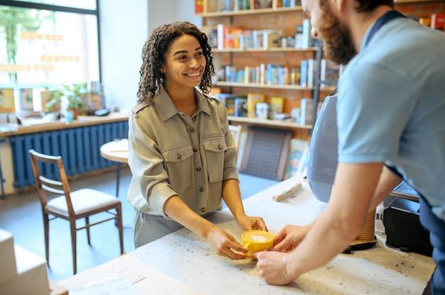 Męski barista w fartuchu daje kawę kobiecie w kawiarni. mężczyzna robi świeże espresso w kafeterii, kelner przy ladzie w barze