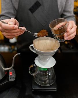 Męski barista wkładający kawę do filtra