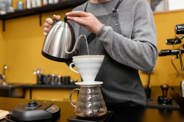 Męski barista z nalewaniem wody w filtrze do kawy