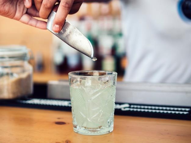Męski barman dodaje lód z miarką