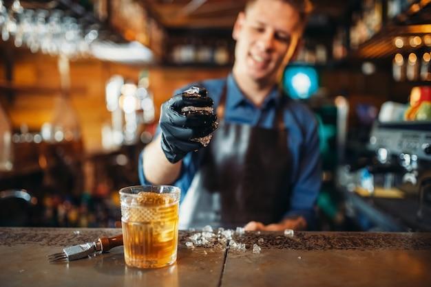 Męski barman pracuje z lodem przy barze