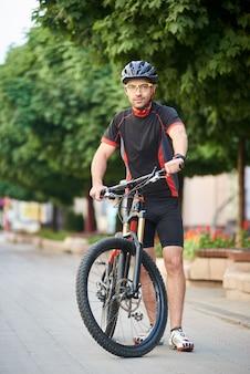 Męski bicyclist stoi blisko roweru w pustej miasto ulicie