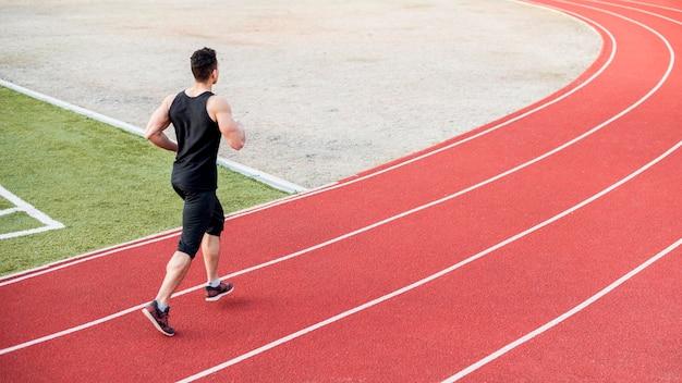 Męski biegacz biega na czerwonym biegowym śladzie