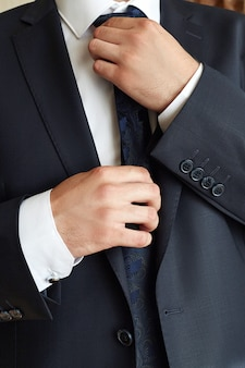 Męski biznesmen koryguje krawat. menedżer nosi