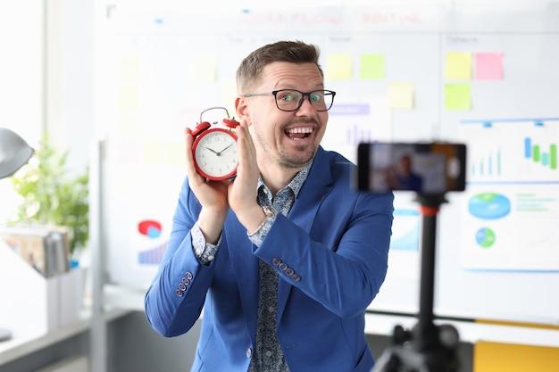 Męski bloger trzyma czerwony budzik i nagrywa filmy edukacyjne, zarządzanie czasem