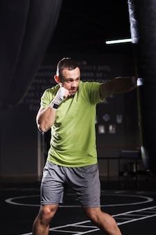Męski bokser noszący koszulkę i szorty ćwiczący z workiem treningowym