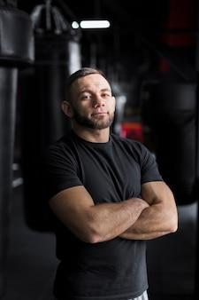Męski bokser pozuje w koszulce z rękami krzyżować
