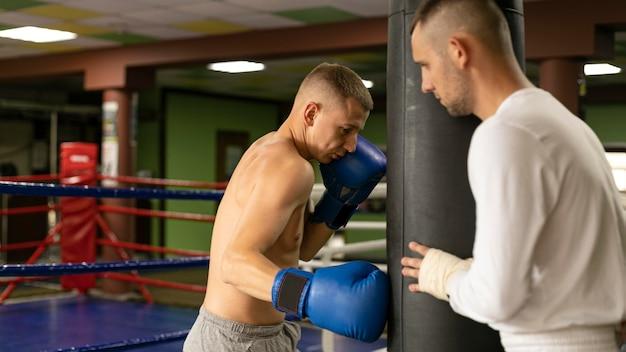Męski bokser w rękawiczkach, trening z człowiekiem