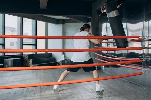 Męski bokser wchodzi na ring i przygotowuje się do walki