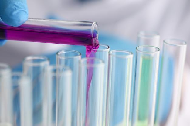 Męski chemik trzyma przepełnioną probówkę szklaną