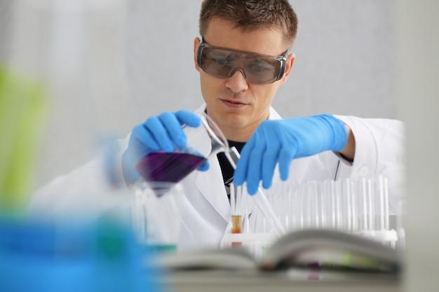Męski chemik trzyma szklaną probówkę w dłoni przelewającej ciekły roztwór