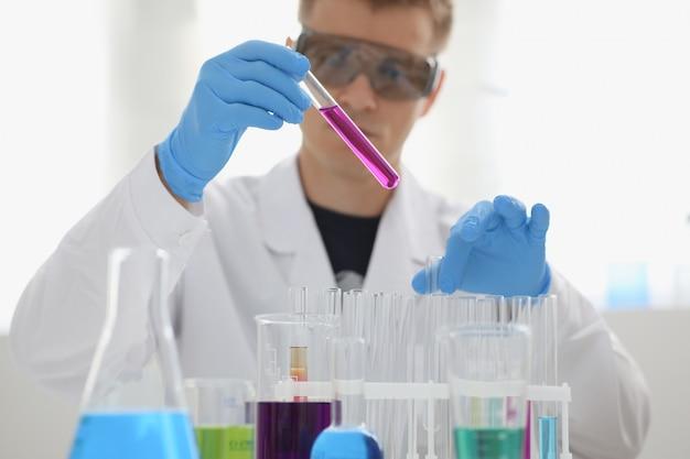 Męski chemik trzyma szklaną probówkę
