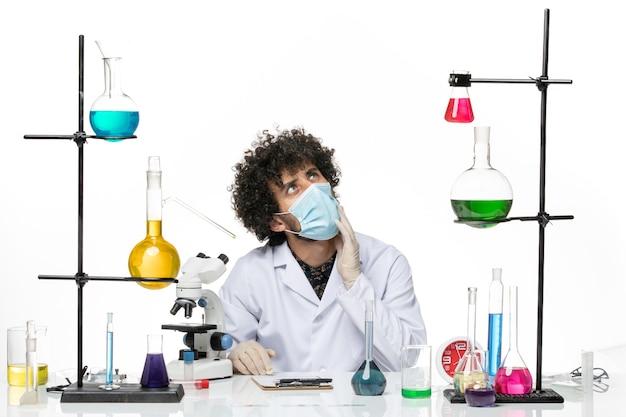 Męski chemik w garniturze medycznym iz maską, siedzący z różnymi rozwiązaniami i myślący na białej przestrzeni