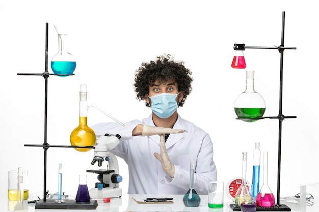 Męski chemik z przodu w kombinezonie medycznym iz maską po prostu siedzący z różnymi rozwiązaniami pozujący na białej przestrzeni