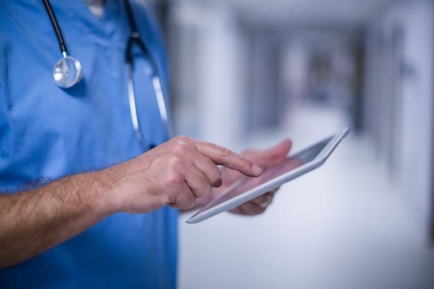 Męski chirurg używa cyfrowego pastylki funkcjonującego pokój