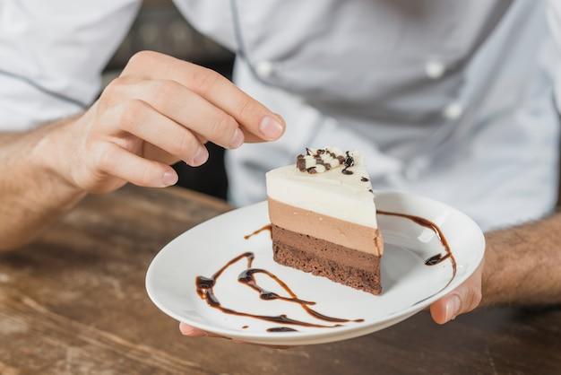 Męski ciasto szef kuchni dekoruje deser w kuchni