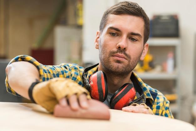 Męski cieśla gładzi drewnianą powierzchnię na piaska papierze