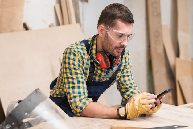 Męski cieśla jest ubranym ochronne rękawiczki patrzeje smartphone
