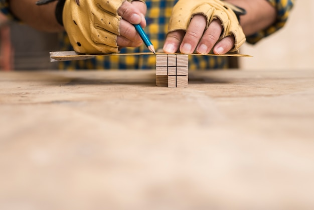 Męski cieśla mierzy blok z władcą i ołówkiem na workbench