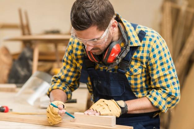 Męski cieśla robi ocechowaniu na drewnianym bloku z ołówkiem