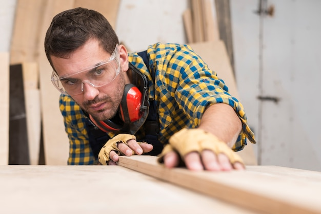 Męski cieśla umieszcza deskę na drewnianej powierzchni w warsztacie