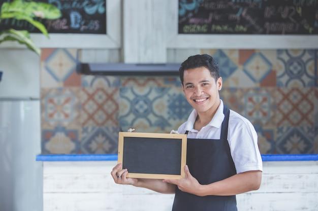 Męski cukierniany pracownik uśmiecha się pustego blackboard i trzyma