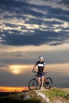 Męski cyklista jedzie rower w góry