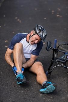 Męski cyklista w bólu trzyma jej ranną nogę