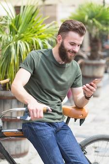 Męski cyklisty obsiadanie na rowerowym używa telefonie komórkowym