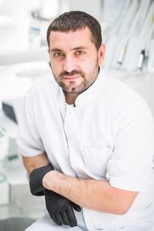 Męski dentysta patrzeje kamerę