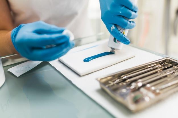 Męski dentysta używa błękitnego silikonowego odciskania materiał