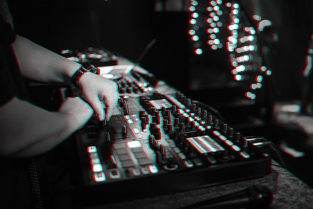 Męski dj miksuje muzykę elektroniczną na profesjonalnym kontrolerze muzycznym w nocnym klubie na imprezie. czarno-białe zdjęcie z efektem usterki wirtualnej rzeczywistości