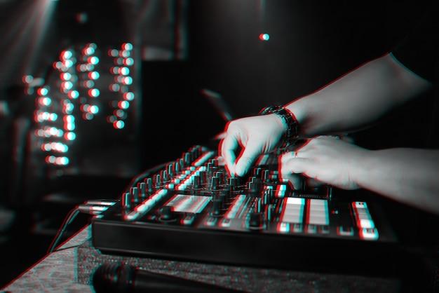 Męski dj miksuje muzykę elektroniczną na profesjonalnym kontrolerze muzycznym w nocnym klubie na imprezie.