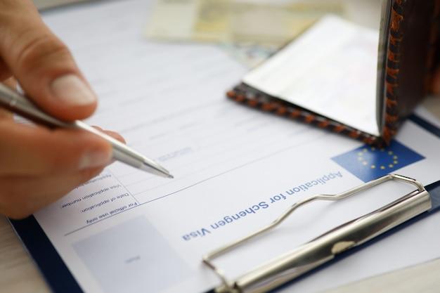 Męski dłoń trzymaj srebrny długopis z paszportem