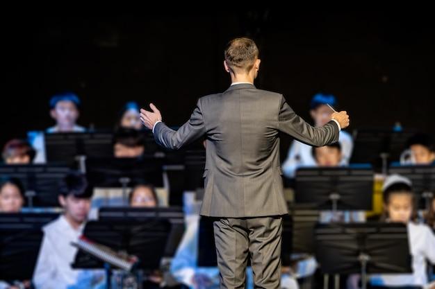 Męski dyrygent dyrygujący jego zespołem koncertowym