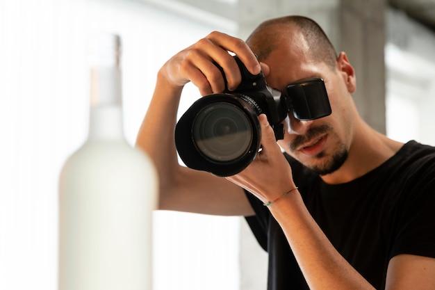 Męski fotograf produktowy wykonuje swoją pracę w studiu