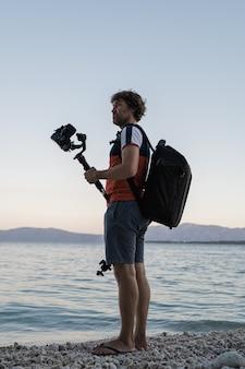 Męski fotograf trzyma jego kamerę na gimbal kiju