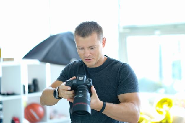 Męski fotograf trzymający czarny profesjonalny aparat w dłoniach w studio