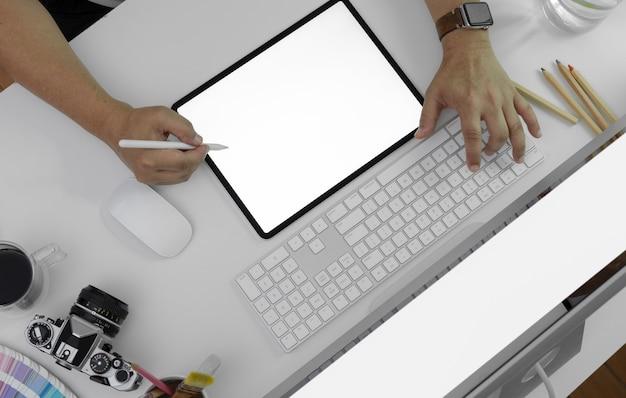 Męski fotograf używa pustego ekranu pastylkę na biurowym biurku z komputerowymi przyrządami, kamerą i innymi dostawami