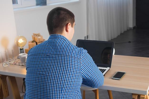 Męski freelancer pracuje z laptopem w domu