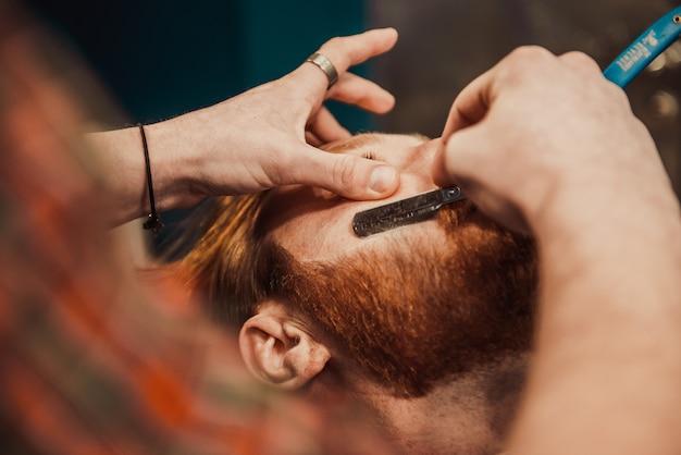 Męski fryzjer goli brodę.