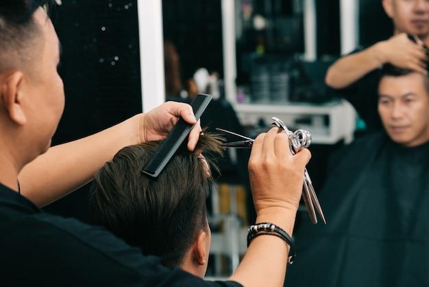 Męski fryzjer obcinający włosy klienta za pomocą komp i nożyczek przed lustrem