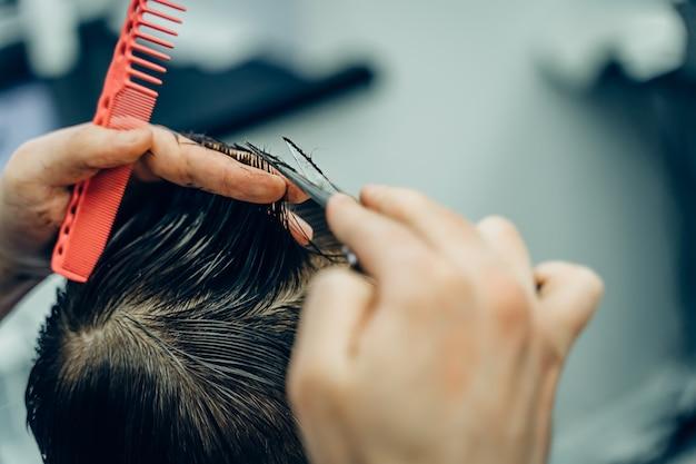 Męski fryzjer ścinający włosy klienta