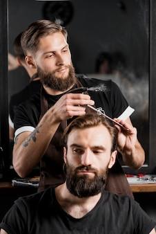 Męski fryzjer tnący klienta włosy w fryzjera męskiego sklepie