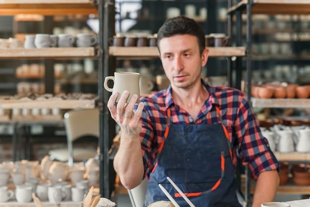 Męski garncarka patrzeje handmade nakrętka podczas dnia pracy w garncarstwie.