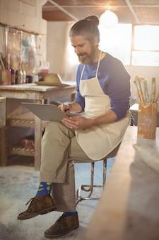 Męski garncarki obsiadanie na stolec używać laptop