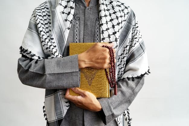 Męski gest trzyma koran i modlitewnych koraliki